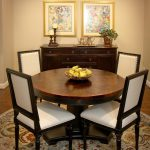 Round Top Wooden Dining Table Dining Chairs Wooden Cabinets Two Wall Arts Round Area Rug With Motifs