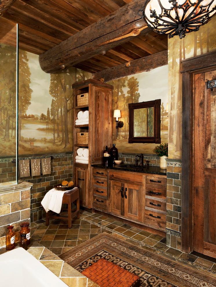rustic vanities in wood planks with black handles, black marble countertop, brown tiles one line backsplash, square wooden framed mirror, sconces