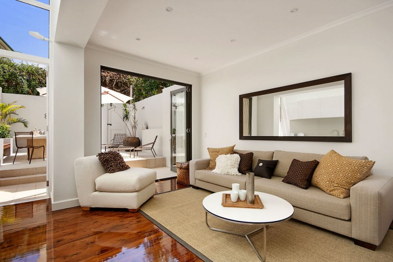semi outdoor living room idea neutral toned couches white top center table in round shape neutral colored rug white walls and ceilings darker wood floors