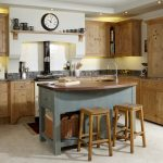 Shabby Look Kitchen Island Wit Grey Body With Shelves, Sinks On Brown Wooden Top, And Brown Wooden Stools