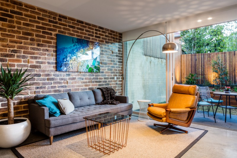simple grey couch yellow leather armchair black glass top table with yellow wires base pale toned area rug red bricks walls curved standing lamp big interior plant