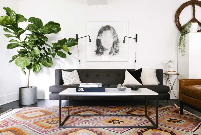 simple living room simple designed couch in black white top center table multicolored area rug white walls artistic painting vivid plant decoration