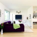 Small Danish Open Concept Living Room With White Walls, Light Hardwood Floors And A Wall Mounted TV Purple Suede Sectional Sofa Light Toned Wooden Floors
