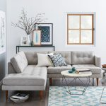 Small Family Room With L Shape Modern Sectional In Grey White & Round Top Center Table With Thin & Light Aluminum Legs Blue White Area Rug Minimalist Black Console Table With Decorative Frames