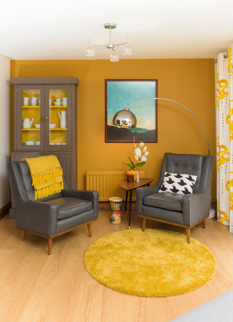 small living room with a pair of grey leather chairs grey finished display storage rounded area rug in yellow yellow walls medium toned wood floors
