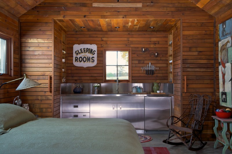 small rustic cabins bed pillow lamp small table wooden walls painting faucet sink small window rocking chair knives bedroom kitchen