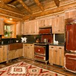small rustic cabins kitchen logs sink faucet wooden wall cabinets stove window fridge flowers dark countertop lamp beautiful room