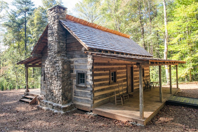 small rustic cabins trees chairs small windows wooden walls small pillars lovely roof old looking exterior