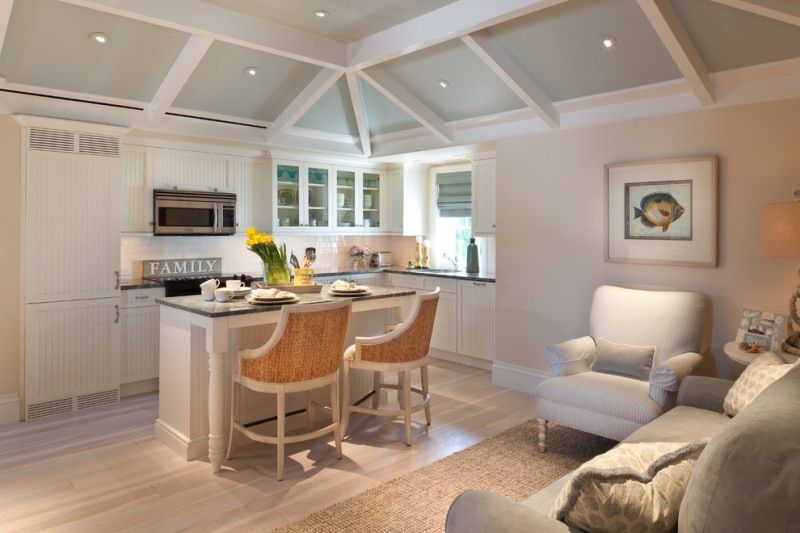 small white kitchen with glossy grey marble contertop and white wooden kitchen island with the same marble, and two white wooden chairs