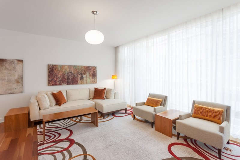 soft & neutral living room set with orange accent pillows simple designed wood tables area rug with modern patterns medium toned wood floors abstract paintings