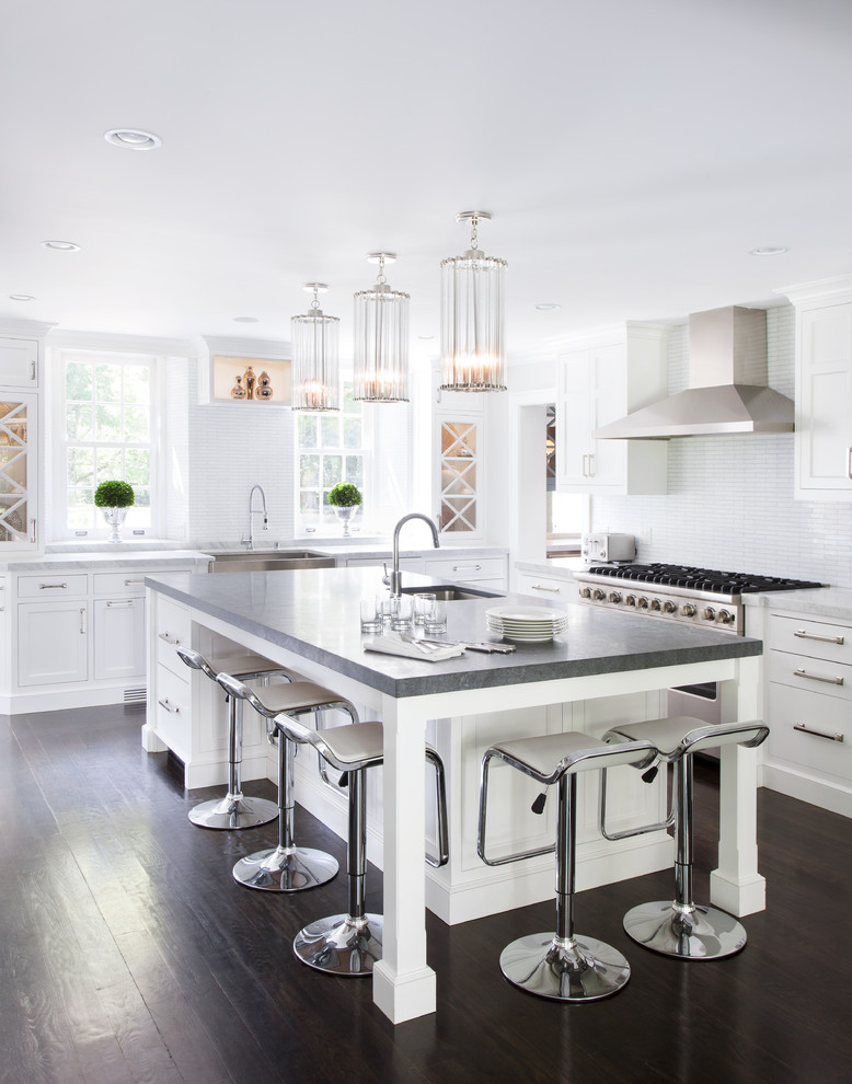 spacious kitchen island with grey marble top, space to store the white bar stools