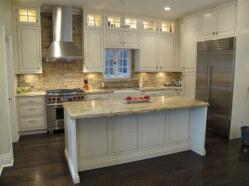 timeless kitchen with stainless steel appliances white island granite countertop natural brick backsplash white cabinets hanging cabinets medium toned wooden floors