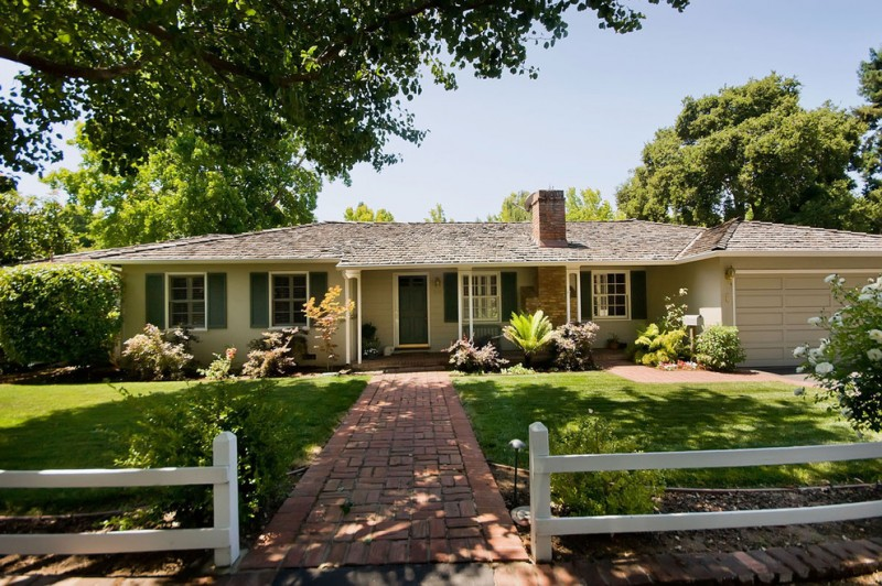 traditional shaded front yard landscape with brick pavers white painted wooden decorative fences gray painted wooden doors and windows glass windows in white frame