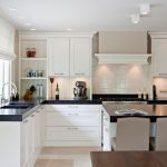 Transitional Kitchen Design With L Shaped Black Countertop White Corner Cabinets Black Top Kitchen Island With Storage And White Chairs Double Sinks White Backsplash
