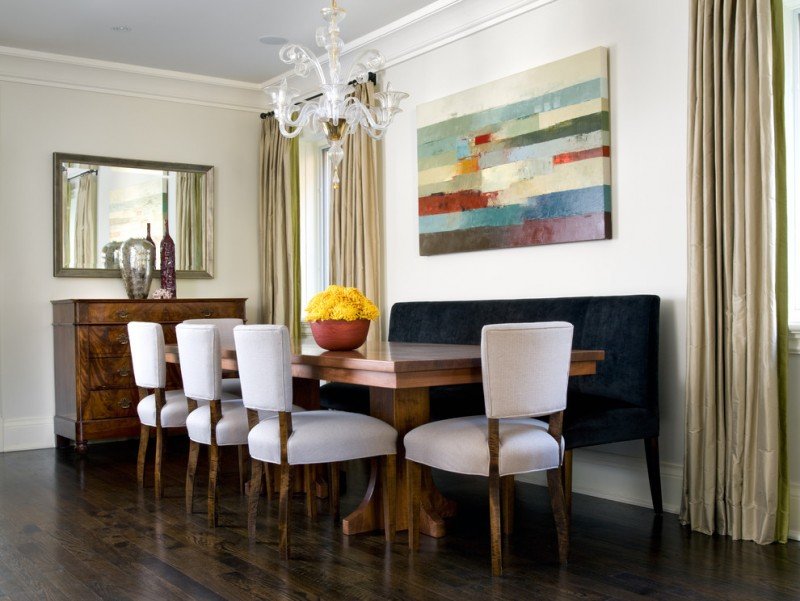 trendy dining room with white walls and dark hardwood floors wooden kitchen table white chairs blue suede benches wooden cabinet cream curtains