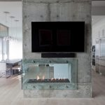 Trendy & Modern Media Room Wall Mounted TV Set Two Sided Modern Fireplace Concrete Fireplace Surround Pale Toned Wood Floors