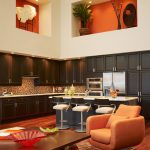Trendy Open Concept Kitchen With Dark Hardwood Corner Cabinets Stainless Steel Appliances Multicolored Backsplash Trendy Kitchen Island With Stools Medium Toned Wood Floors