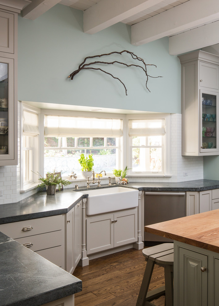 white corner cabinet over the farmhouse sink in white dark gray countertop wood top kitchen island with storage and stools medium toned wood floors blue walls with decorative tree branches