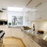 White Corner Cabinet Under Sink And Frameless Glass Window Large Stainless Steel Countertop White Ceramic Tiles Backsplash Pale Toned Wood Floors Without Finishing Stainless Steel Appliances