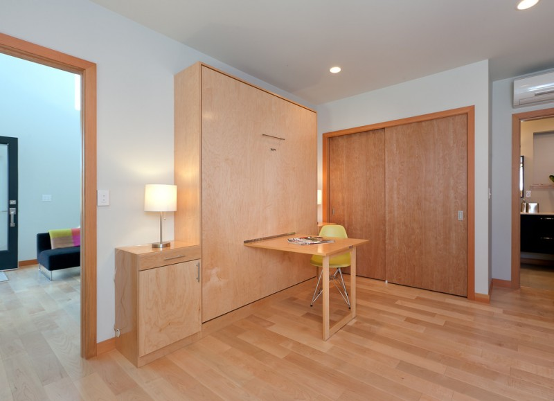 wood table inserted into a murphy bed recessed closet with wood door wood bedside table with modern lamp