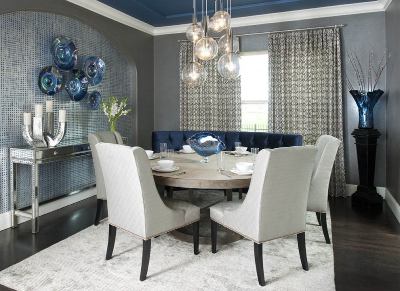 Blue settee white chairs wooden round kitchen table white rug medium toned wooden floors chandelier lamps candle holder metal surface cabinet