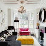 Contemporary Living Room With White Walls And Black Sofa, A Standard Fireplace, Wall Artworks Chandelier Lamp Red Accent Sofa Yellow Velvet Upholstery Table Standing Lamp Floating Cabinets