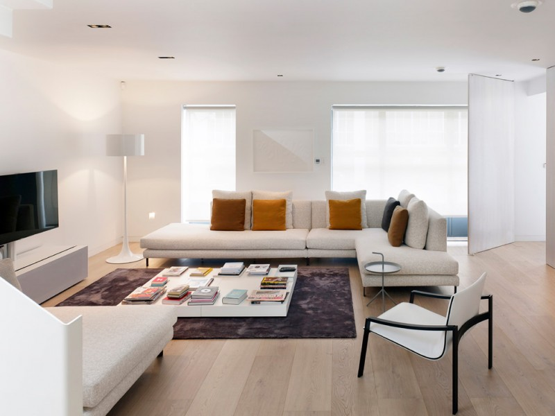 Danish formal living room with white walls, light hardwood floors, a freestanding TV and beige floors white chairs and sofa brown toned pillow throws