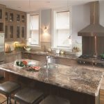 Elegant L Shaped Kitchen With Glass Front Cabinets, Stainless Steel Appliances, A Drop In Sink And Light Wood Cabinets Leather Chairs Medium Toned Wooden Floors