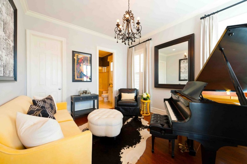 Elegant living room with a music area square mirror chandelier lamp black and white animal printed rug yellow sofa pillow throws medium toned wooden floors
