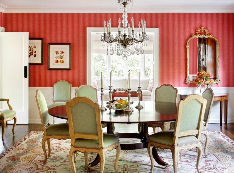 French style dining chairs with light green fabrics and wood frames dark finishing table in round top shape area rug with traditional motifs red and white walls traditional hall console