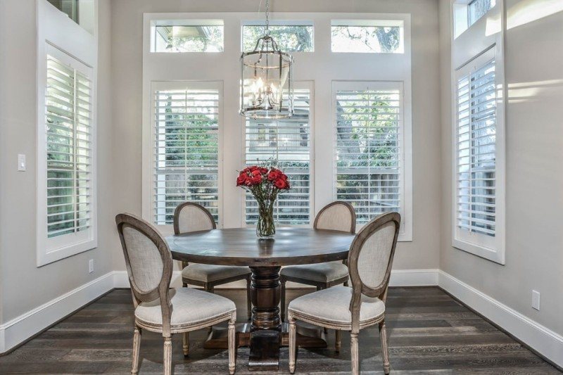 French style dining room with white French style dining chairs with shabby wood frames round top wood dining table glass vase with red roses decoration shabby but cool wood floors