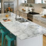 L Shaped Eat In Kitchen With Laminate Countertops, White Backsplash And Stainless Steel Appliances Turquoise Bar Stools Light Toned Wooden Floors A Drop In Sink