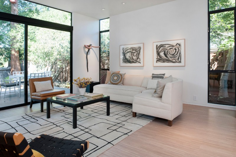 L shaped sectional in white tribal covered throw pillows square shaped glass top table with black legs small leather chair with black legs white area rug with thin line motifs