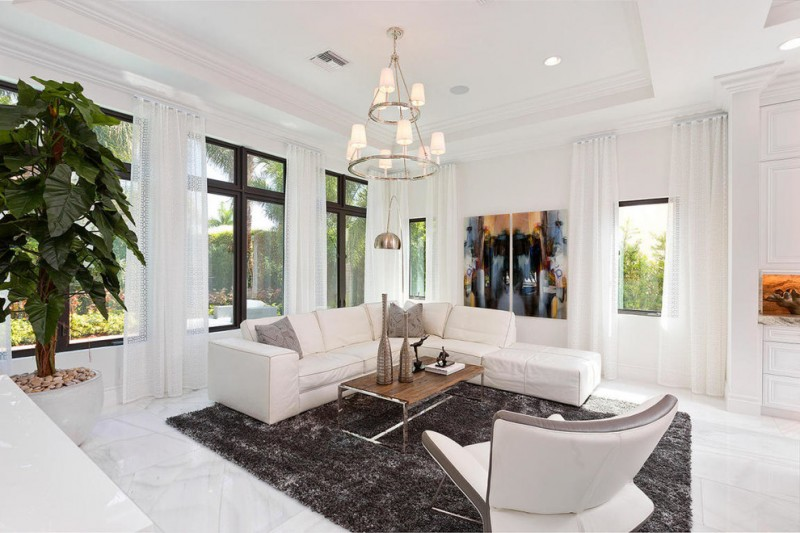 L shaped white sectional with throw pillows industrial coffee table modern white chair fluffy black area rug white floors large glass windows with floor to ceiling white draperies