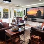 Mid Sized Elegant Family Room With Gray Walls, Medium Tone Hardwood Floors And A Wall Mounted TV White Painted Cabinet Brown Leather Sofa Wooden Table White Doors And Trim