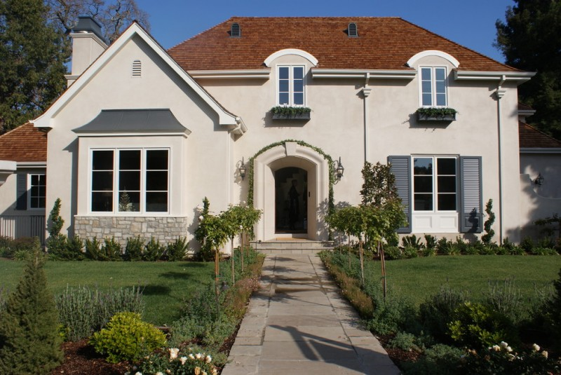 Mid sized traditional exterior home with brown roofs and white wall gray windows doors arched front doors big glass windows exposed stone mortar