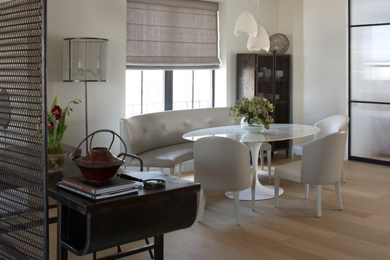 Oval glass dining room table with white chairs and curved settee light toned wooden floors white wall stainless steel appliances standing lamp pendant lamps roman shade