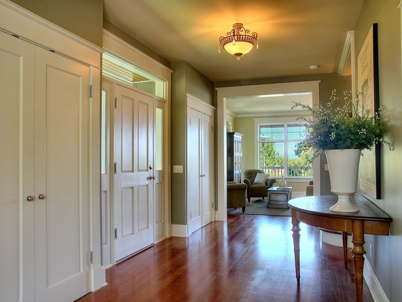 Traditional entry hall with green walls and medium tone hardwood floors chandelier lamp vase table wooden table white doors and trim