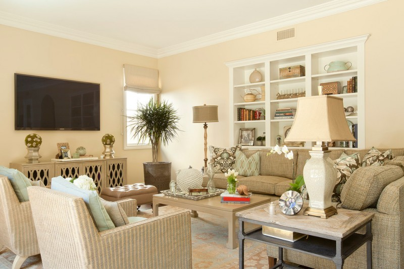 Traditional family room with beige walls and a wall mounted TV white table lamp and standing lamp white table beige sofa multicolored pillow throws
