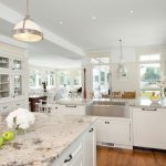 Traditional Kitchen Idea With A Farmhouse Sink And Laminate Granite Countertops White Painted Cabinets Medium Toned Wooden Floors White Chairs Wall Mounted TV