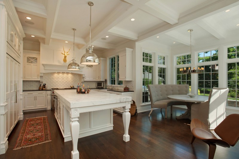 Traditional u shaped eat in kitchen with recessed panel cabinets, white cabinets, white backsplash and subway tile backsplash, accent rug, medium toned wooden floors