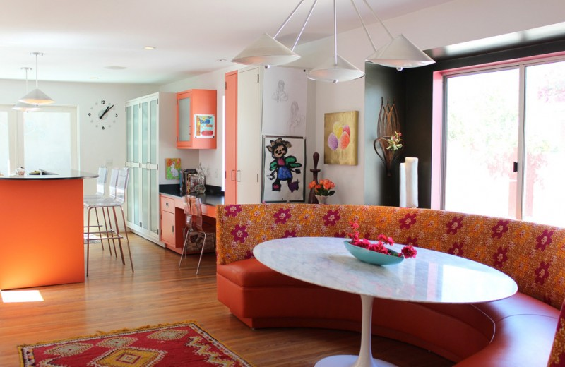 Trendy eat in kitchen photo with flat panel cabinets and orange cabinets red rug medium toned wooden floors white pendant lamps black and white walls