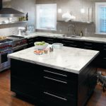 Trendy Kitchen With A Drop In Sink, Stainless Steel Appliances, Black Cabinets And Laminate Countertops Medium Toned Wooden Floors Silver Appliances