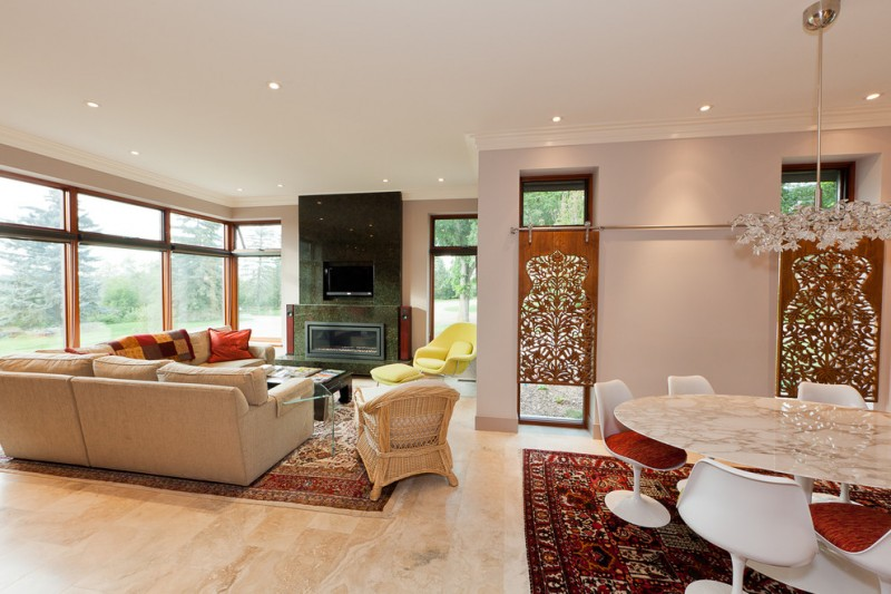 Trendy living room with beige walls and a ribbon fireplace carved wood panels on glass sliding doors rattan chair granite tiles and table beige sofa multi colored pillow throws accent rugs