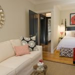 Trendy Master Bedroom With Beige Walls And Medium Tone Hardwood Floors White Sofa Multi Colored Pillow Throws Dark Painted Doors Cream Rug