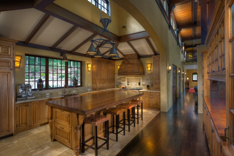 Tuscan kitchen design with wooden raised panel cabinets and wood countertops wooden bar stools medium toned wooden floors ceramic tiles bronze pendant lamp