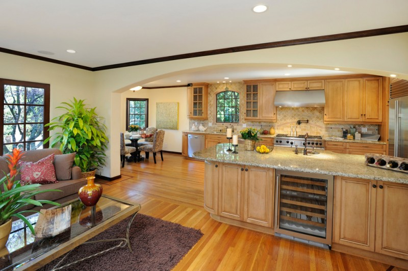Tuscan kitchen with raised panel cabinets and stainless steel appliances carpet glass coffee table floating cabinets brown sofa red pillow throws