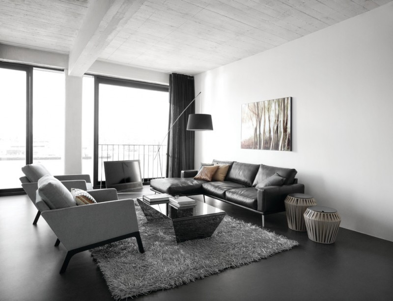 black and white modern living room set consisting of black leather sofa two white chairs modern black glass coffee table fluffy grey area rug black laminated floors modern floor lamp