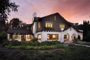 brown Stucco two story exterior home with Roman arches white wall brown chocolate gable roofs sage green window trim stairs pathway