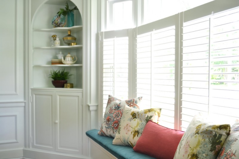 built in bench under bay window equipped with foam covered with blue textile accent pillows built in corner cabinet in white with curve top and waved individual shelves